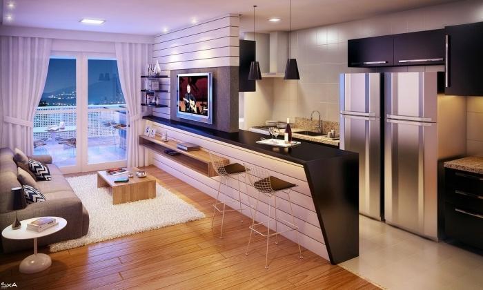 petite cuisine équipée, carrelage blanc, frigo gris, meuble cuisine noir, un ilot central blanc avec plan de travail noir, canapé gris, tapis blanc et table basse minimaliste en bois