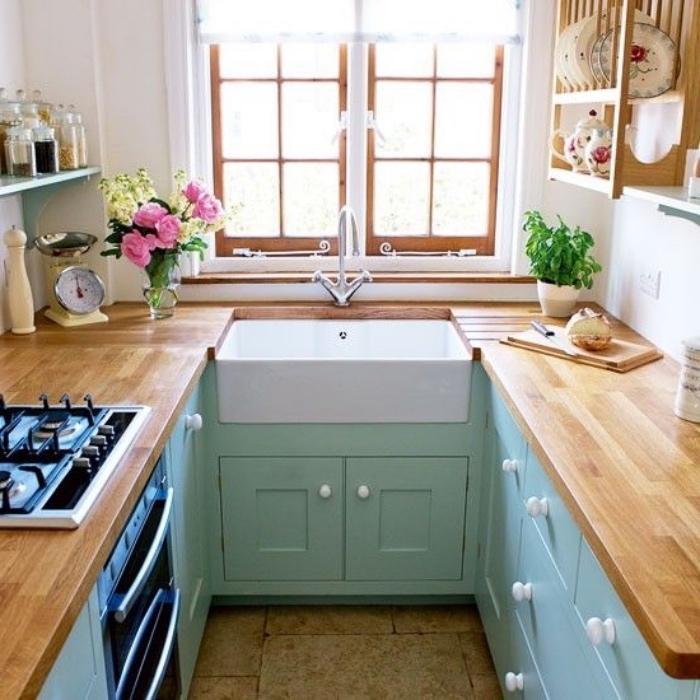 idée de façade cuisine vert mint avec un plan de travail en bois, étagères en bois rangement vaisselle, épices, decoration de fleurs, revêtement sol en pierre