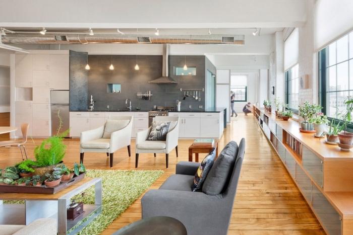facade cuisine blanche avec crédence grise effet béton, parquet en bois clair, ouverture sur salon avec canapé gris et chaises blancs, table en bois et metal, deco de plantes, détails industriels, cuisine americaine