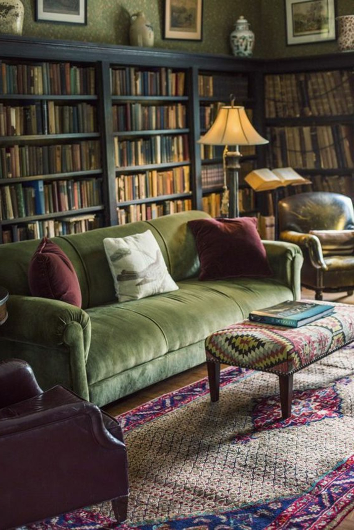 coussins et fauteuil couleur aubergine, lampe design ancien, grande bibliothèque murale