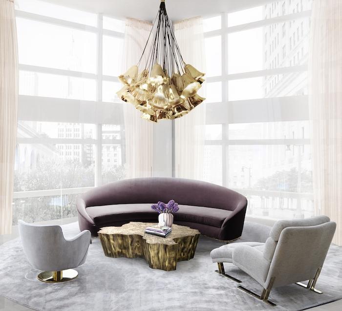 lampe cuivre, tapis en velours gris, fenêtres surdimensionnés, rideaux longs en beige, plafond blanc, canapé en velours violet