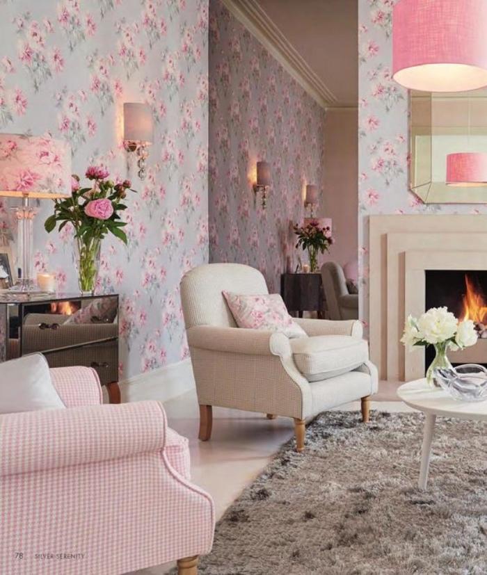 tapis gris, papier peint bleu à fleurs rose, fauteuil gris et fauteuil rose, table basse blanche, cheminée romantique, bouquets de fleurs