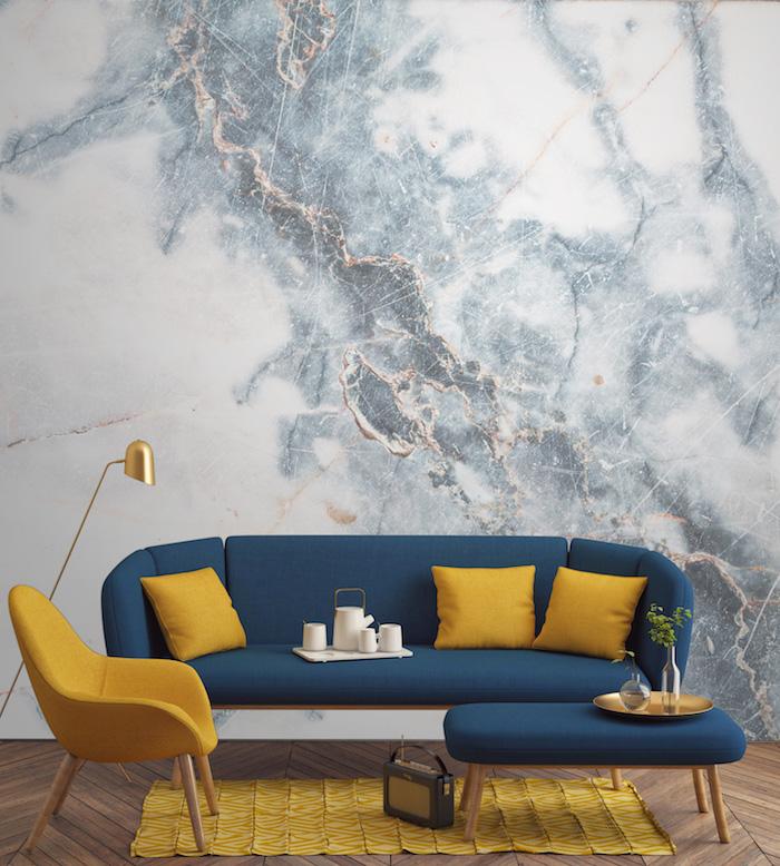 marbre blanc, aménagement de salon, revêtement de sol en bois, canapé en bleu foncé avec coussins jaunes, lampe sur pied en cuivre