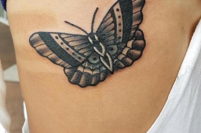 tatouage symbolique, dessin sur le corps féminin, tatouage à design papillon noir