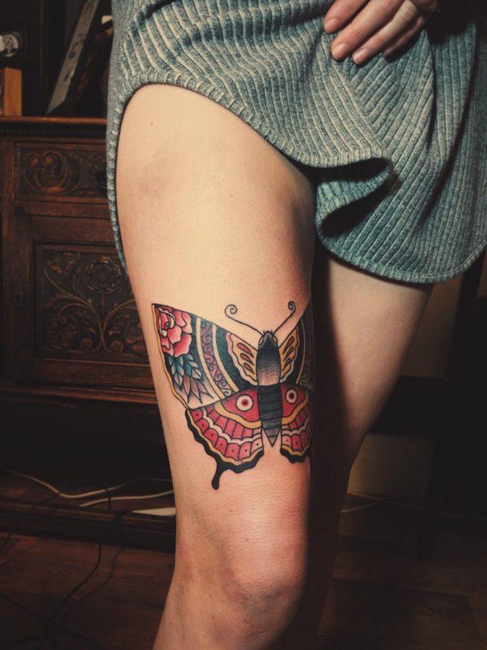 tatouage couleur, idée dessin en encre sur la peau, tatouage papillon avec ailes à motifs floraux rouges