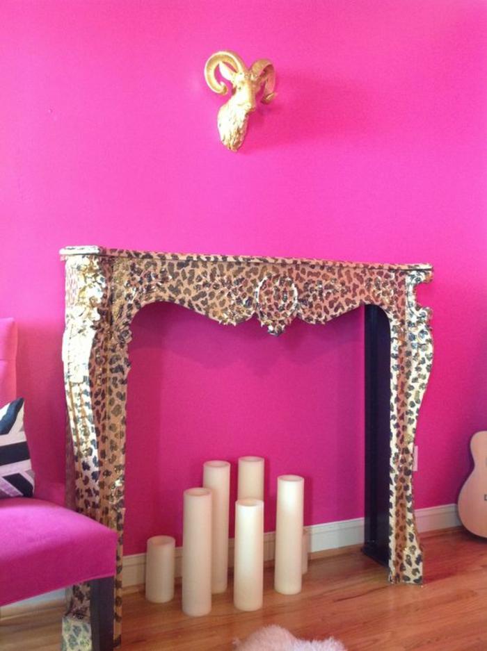 couleur magenta fuchsia sur le mur avec utilisation d un element de cheminee aux prints leopard et decration avec des grandes bougies blanches