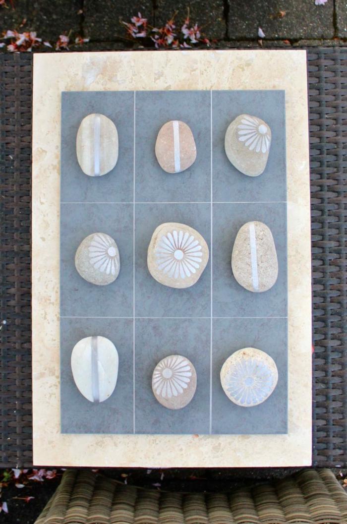 des galets décorés à la peinture argentée à utiliser dans un jeu de morpion improvisé