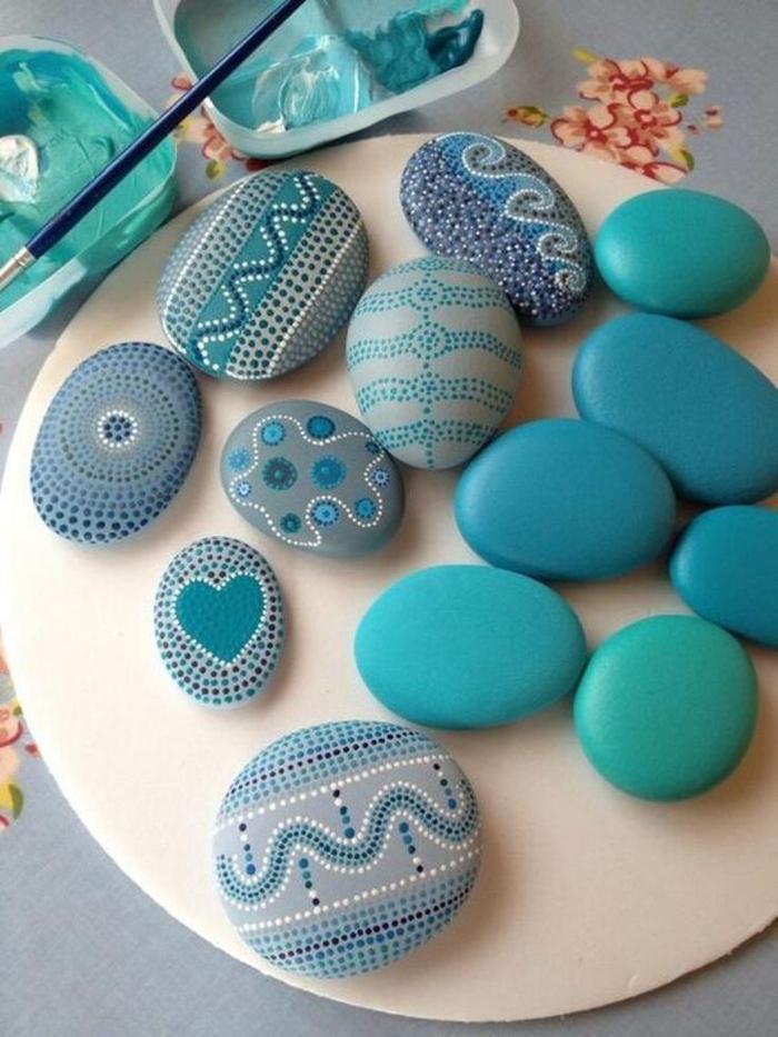 des galets peints aux différentes nuances de bleue au design en petits points