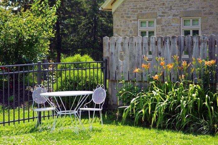 aménager son jardin, idée de gazon vert, chaises et table en metal, une palissage en bois avec une parterre de fleurs, maison de campagne