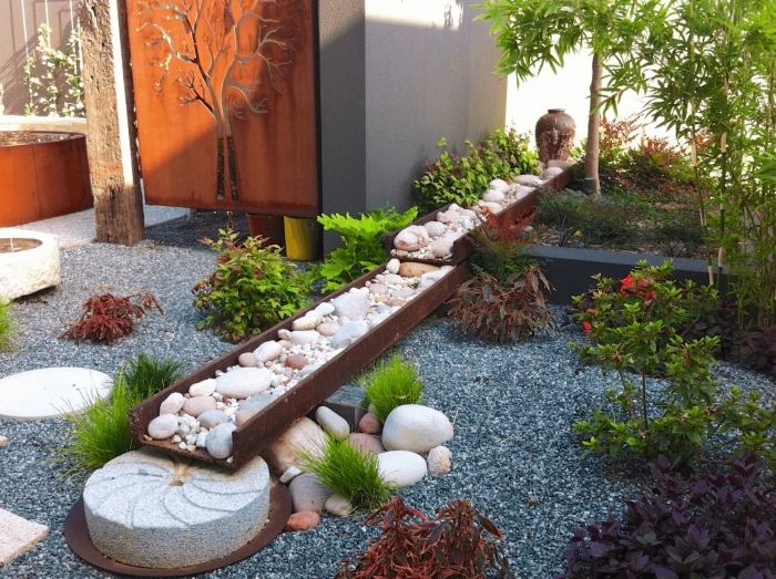 une rivière en pierre et sol en gravier, arbustes et bambou, idée amenagement jardin zen minimaliste