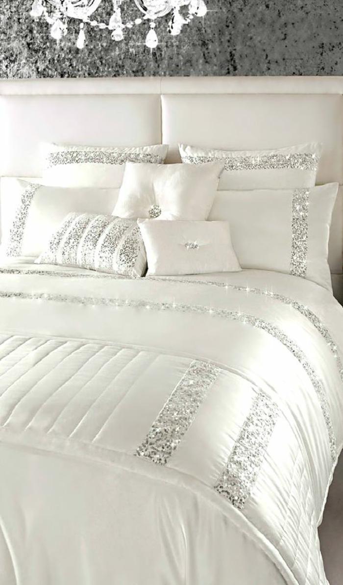 peinture gris perle lit en blanc aux bandes décoratives en gris pailleté avec un grand lustre brillant