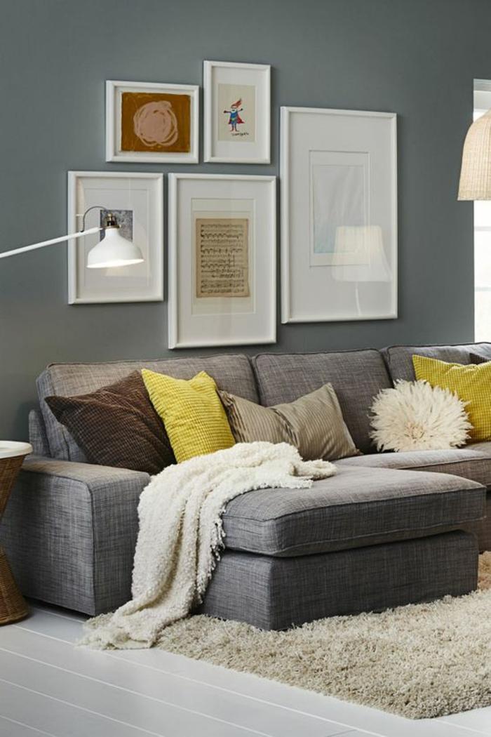 couleur gris perle mur nuance foncée avec plusieurs tableaux de taille différente canapé aux coussins jaunes