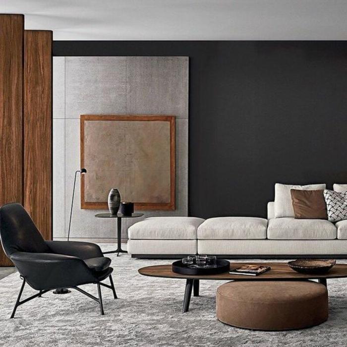 idée aménagement salon, chaise noire, table en bois et tabouret marron clair, tapis gris
