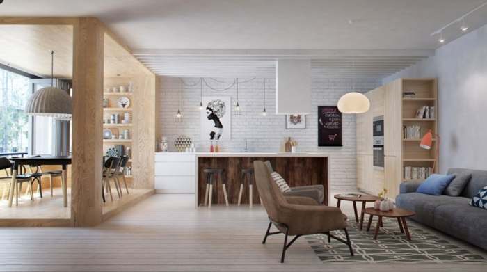 aménager une petite cuisine, blanche avec ilot central en bois et plan de travail blanc, suspension ampoules, ouverture sur salon avec canapé, tapis et fauteuils gris, table basses gigognes en bois, parquet blanchi, salle à manger dans un cube en bois