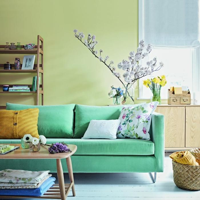 canapé couleur vert d eau dans un salon couleur peinture vert pistache, parquet blanchi, table basse en bois, panier de rangement et étagère en bois