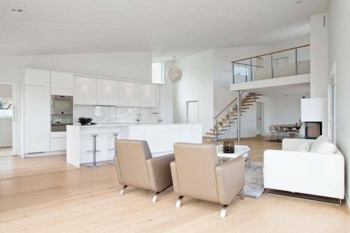 cuisine ouverte sur salon, modèle de cuisine blanche avec ilot central blanc, parquet clair, salon avec canapé et table basse blanche, fauteuils gris