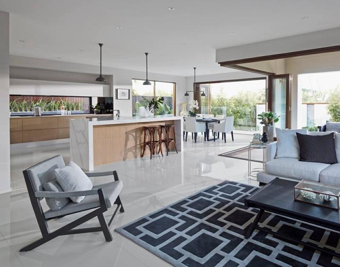 cuisine ouverte sur salon, meuble cuisine en bois, ilot central en bois avec plateau en marbre, revêtement sol carrelage blanc, salon canapé blanc, tapis gris, table basse noire, chaise grise
