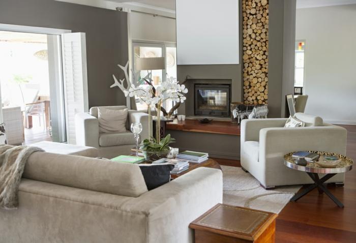 idée déco salon moderne, range-buche décoratif, sofas gris, sol en bois, grands canapés