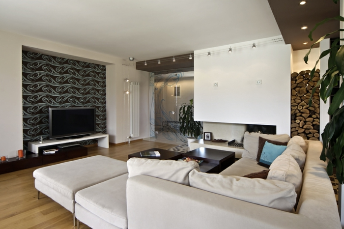 idée deco salon moderne, grand sofa modulable, sol aspect bois, plusieurs lampes installées au plafond, range-bûche déco