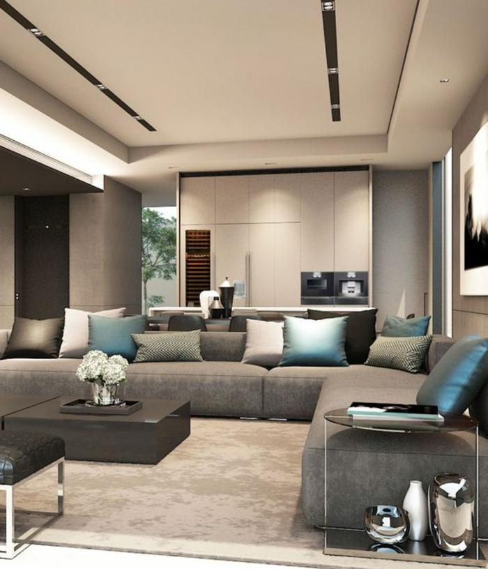 idée décoration salon, canapé modulable, plusieurs coussins bleus, tapis taupe