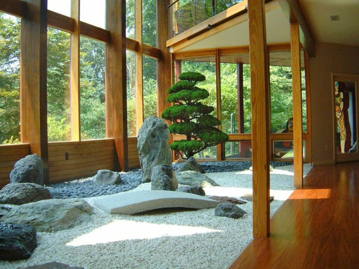 jardin zen a l interieur d une maison charpente en bois, gravier, galets et pierres, imitant des montagnes, arbre japonais, grosses fenêtres