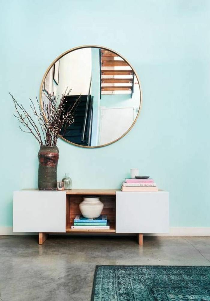 peinture vert d eau sur le mur, grand miroir rond, meuble de rangement, revêtement aspect béton, tapis bleu canard et branches dans un vase