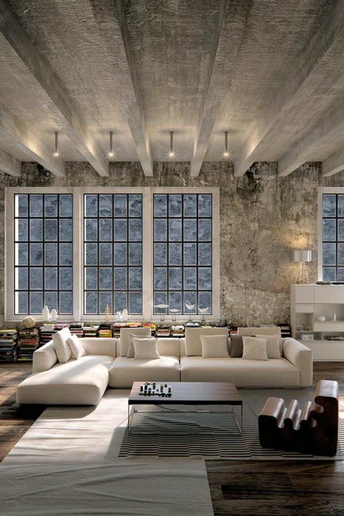 idée deco salon, plafond en béton style industriel, sofa couleur claire, livres au sol