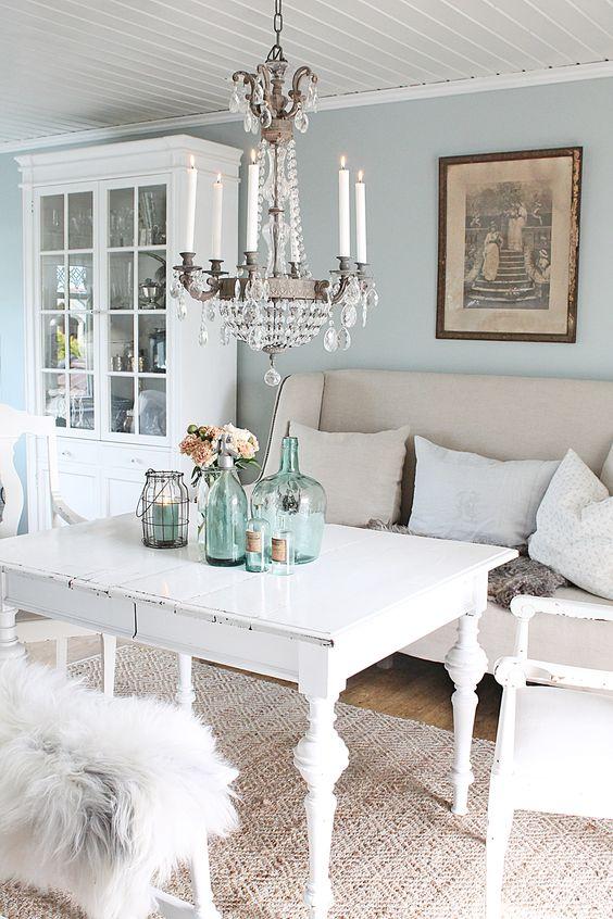 salon shabby chic decoration, table et chaises blanches, mur couleur bleu pastel, lustre élégant, decoration de table bouteilles en verre, vaisselier blanc