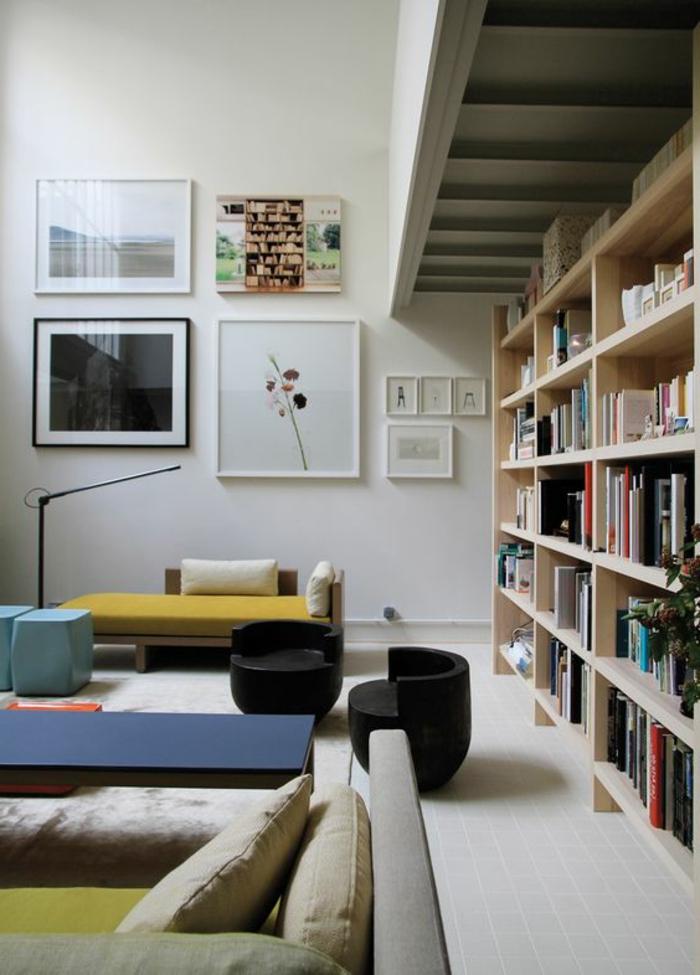 idées déco salon, étagère bibliothèque en bois, peinture gris pâle et tableaux décoratifs, mobilier en bois avec coussins