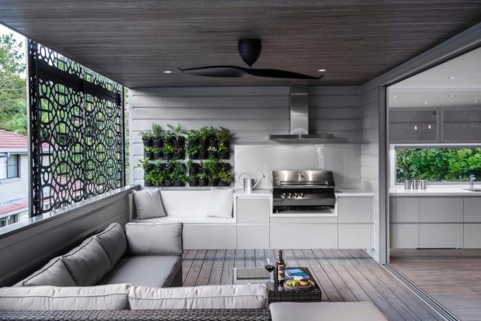 amenager petite cuisine blanche, avec aspirateur inox, parquet et canapé gris avec un mur végétale verte pour une touche zen, table basse en rotin