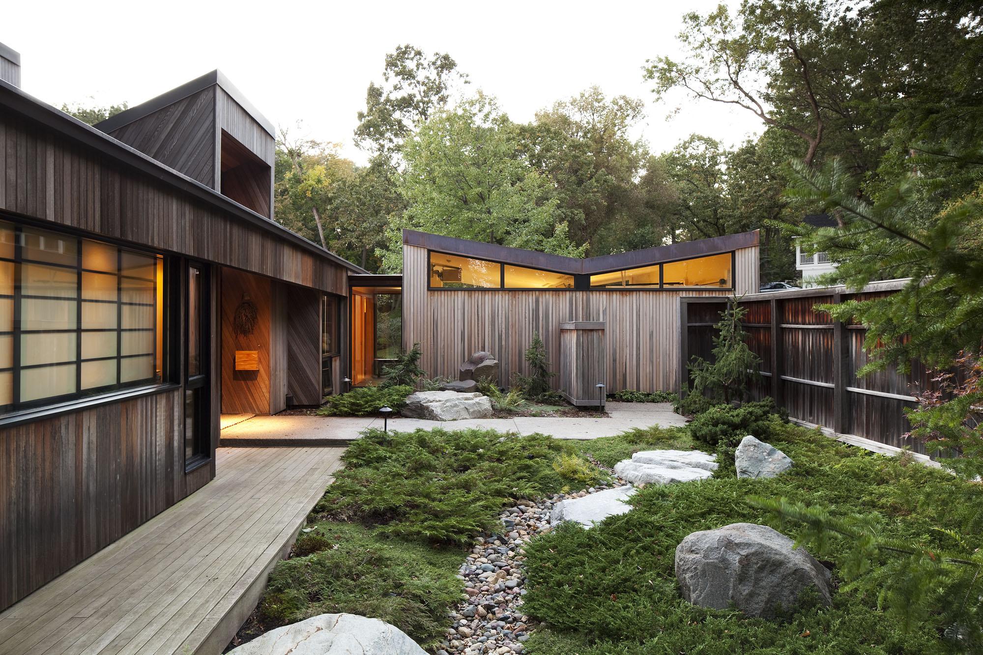 idée de maison moderne avec un jardin zen, chemin de galets, plante couvrant sol et grosses pierres, clôture en bois