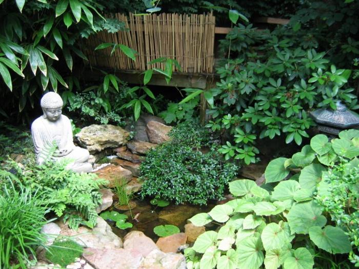 déco de jardin zen, un petit bassin d eau, fontaine, entourée de pierres, statue bouddha, vegetation verte