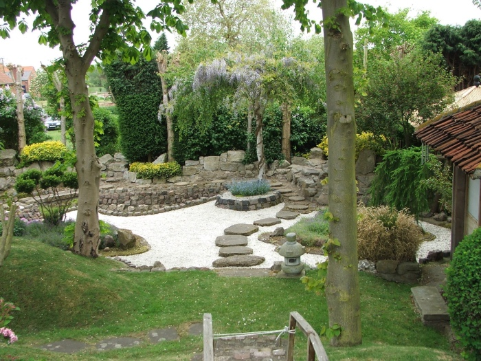 modele amenagement jardin zen, pelouse avec des arbres, chemin de pierres, lanterne, gravier blanc, arbres et buis, vegetation verte en profusion