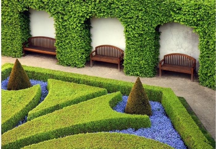 exemple comment paysager son jardin à la française, labyrinthe de buis, avec des fleurs violettes, bancs en bois, mur enveloppé de lierre