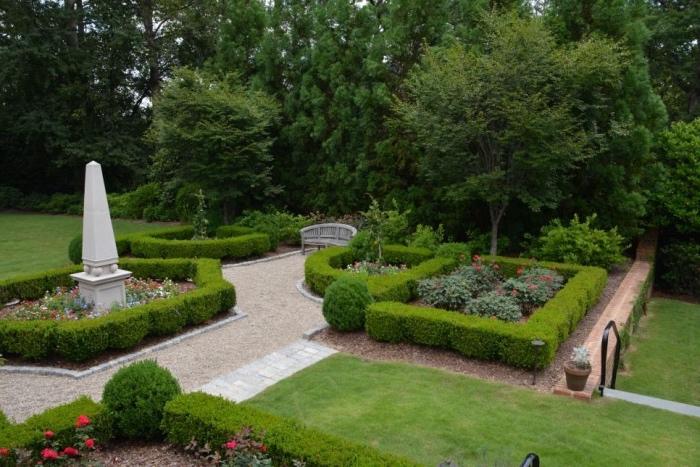 idee jardin amenagement, plusieurs espaces verts, gazon, buis rosiers et autres arbustes, fleurs dans un ajrdin à la française avec une sculpture