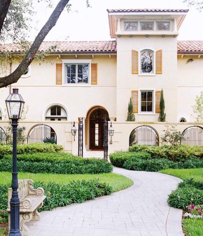 idee deco jardin, chemin de dalles de béton, gazon avec des arbustes et des fleurs, banc en pierre antique, maison style méditerranéen