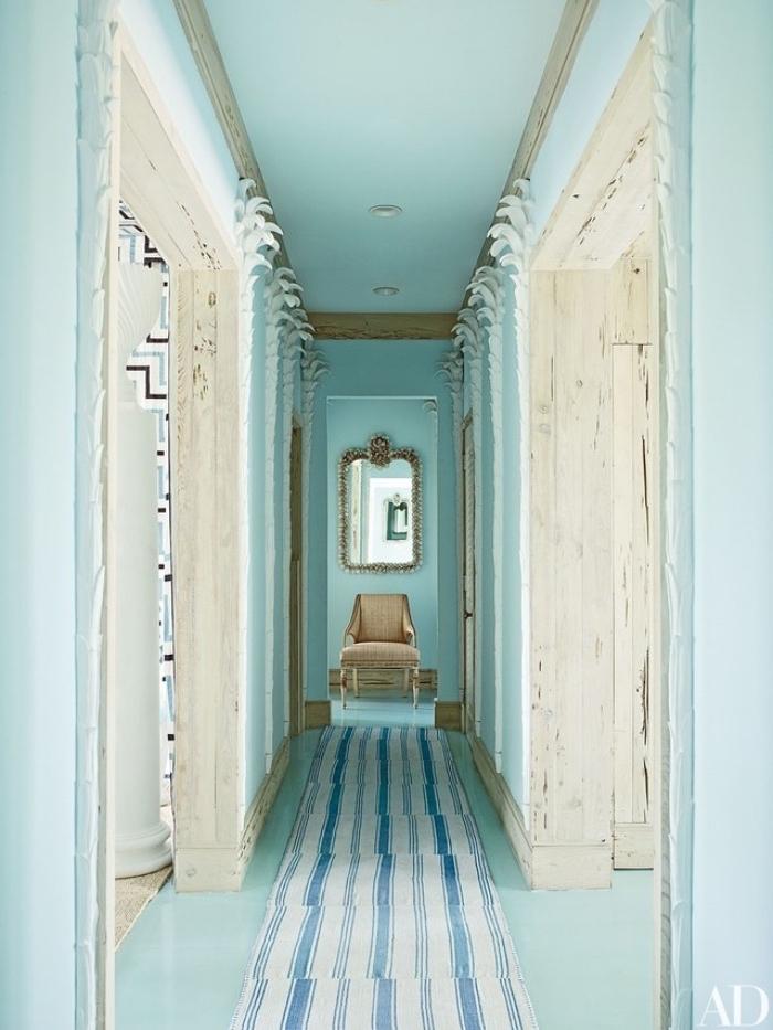 couloir couleur vert pastel et blanc, tapis à rayures blancs et bleus, un fauteuil beige au fond et miroir baroque