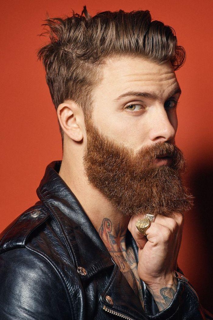 modele de coiffure, veste en cuir noir homme, tatouage sur les bras et le cou design homme, barbe longue châtain cuivré