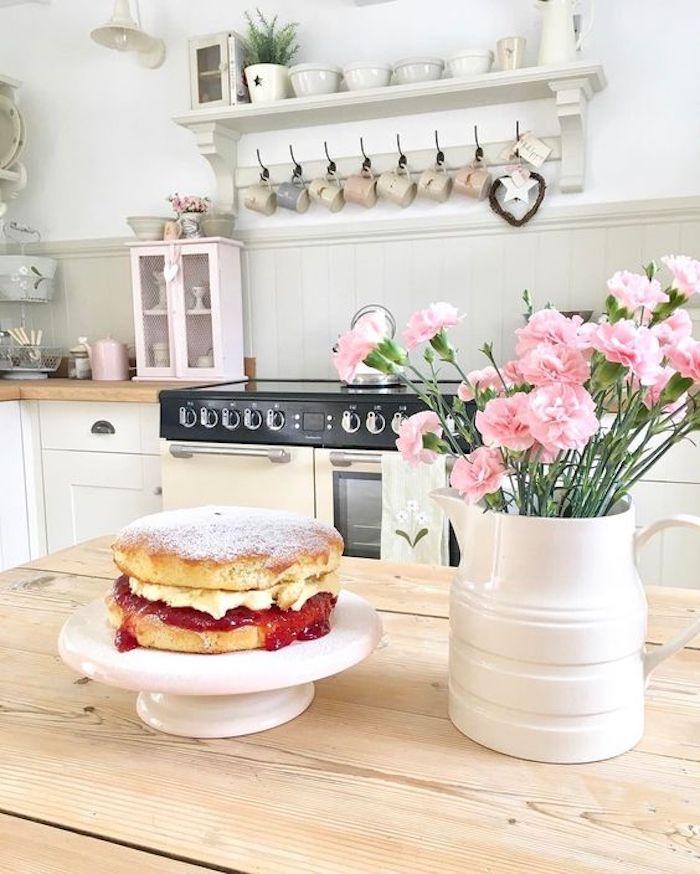 shabby chic dans la cuisine, table en bois clair, façade cuisine blanche, plan de travail en bois, crédence grise, étagère blanche rangement vaisselle, bouquet de fleurs rose