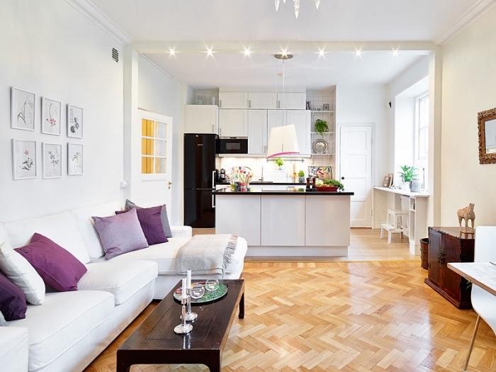 modèle idée cuisine ouverte en blanc et noire avec ilot central blanc et plan de travail noir, parquet clair, canapé blanc et coussins violettes, table basse en bois rustique