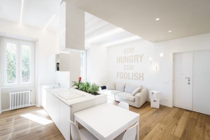 idée amenager petite cuisine blanche ouverte sur un salon constitué de canapé blanc, parquet clair, sticker mural citation