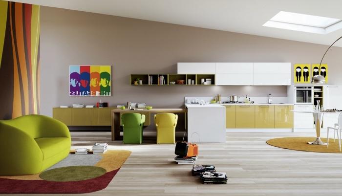 aménager une petite cuisine ouverte sur un salon et une petite coin repas, facade cuisine jaune et blanc, ilot comtoir en bois, salon canapé vert pistache et tapis coloré, parquet clair, panneau decoratif pop art