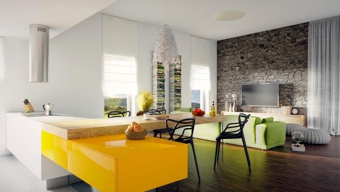 cuisine ouverte sur salon, couelur blanche et jaune et bar en bois clair avec des chaises noires, parquet marron, salon en canapé vert pistache et tv sur un mur d accent papier peint imprimé imitation pierre, piles de livres