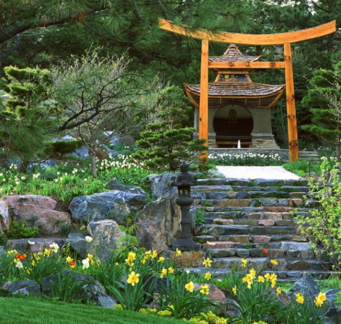 idée de jardin zen adjacent à un temple japonais, escalier en pierre, entouré de grosses pierres, pelouse et fleurs fraiches