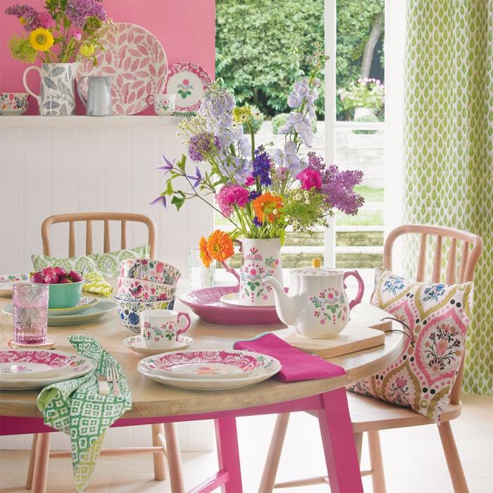 décoration shabby chic salle à manger, table palteau en bois clair et pieds rose, chaises en bois clair, mur couleur rose poudré, vaisselle shabby chic à motifs floraux, rideaux vert pistache, bouquet de fleurs