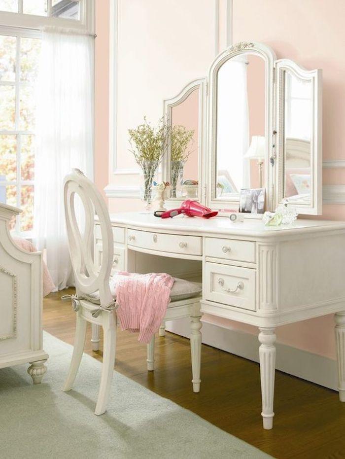 coiffeuse blanche, chaise et miroir, lit blanc baroque, tapis gris, mur couleur rose pastel, rideaux blancs, grandes fenêtres