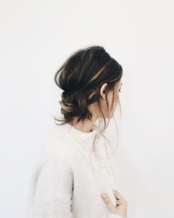 exemple de chignon bas décoiffé réalisé à partir une tresse, mèches libres de coté, coiffure simple et rapide boheme