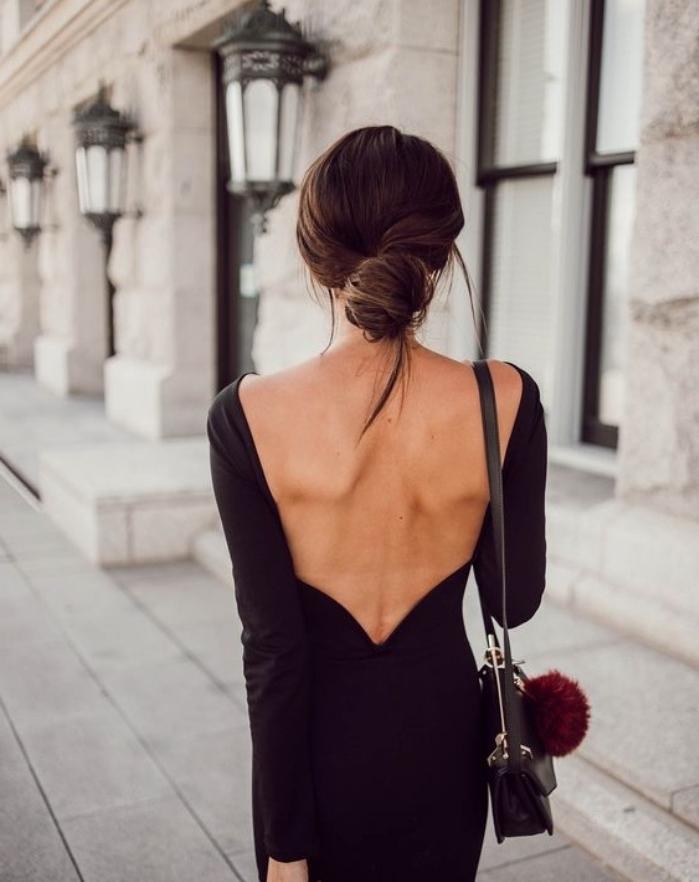 chignon bas décoiffé, femme cheveux long, chatain foncé, une robe longue noire, petit sac à main stylé, look branché