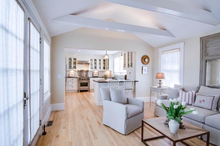 aménager une petite cuisine blanche classique, ouverture sur un salon avec des poutres apparentes blanches, canapé et fauteuil gris et table basse en bois, parquet clair