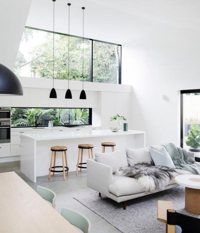 cuisine ouverte sur salon avec façade cuisine et ilot blanc, revêtement sol, effet béton, tapis gris, canapé blanc cassé, coin salle à manger avec table et chaises en bois